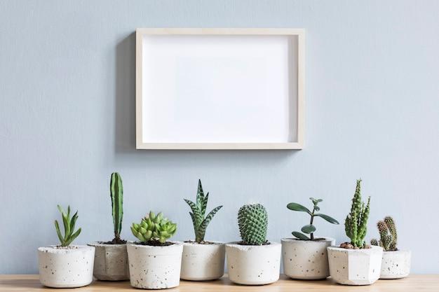 Минималистичный домашний интерьер с фоторамкой на коричневом столе с композицией из кактусов и суккулентов на деревянной детали в стильных цементных горшках