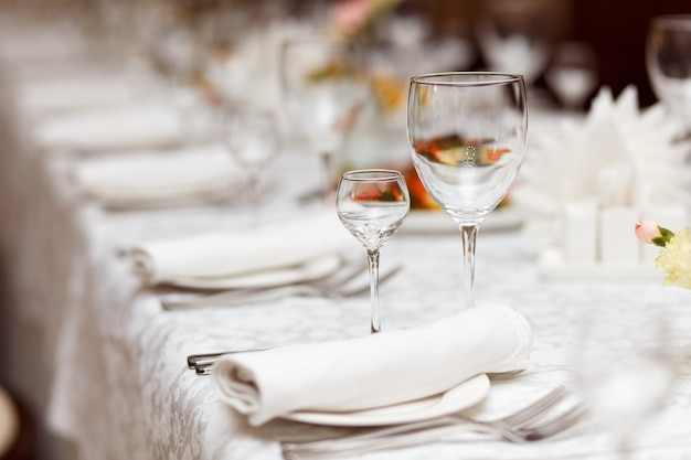Minimalistic image of glasses for alcoholic beverages on a table set for celebration