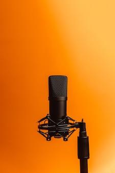 Минималистичное изображение потокового микрофона на оранжевом фоне с копией пространства, минимальная концепция