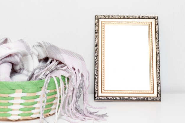 Minimalistic interior design with photo frame and a basket with warm woolen clothes on a desk