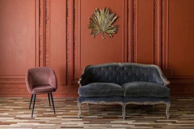 Минималистичный интерьер гостиной комнаты в классическом стиле с copyspace. красная штукатурка стен украшена молдингами и золотой пальмовый лист, диван и диван на деревянном полу.