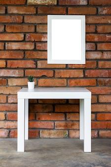 벽돌 벽에 흰색 테이블과 흰색 액자가 있는 미니멀한 인테리어