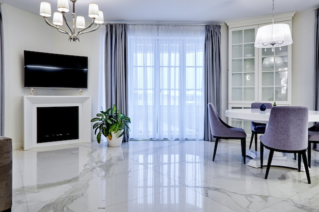 Minimalistic interiorliving room in light tone with marble flooring, large windows and a table for four persons