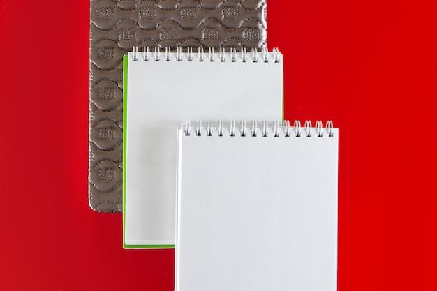 デザインのミニマルなレイアウト赤い背景にメモ用の空白のノートブックを開く