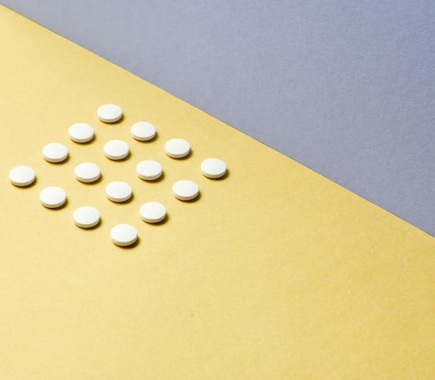 최소한의 의료 개념. 파스텔 컬러 배경에 동일한 흰색 정제의 그룹입니다. 평면도