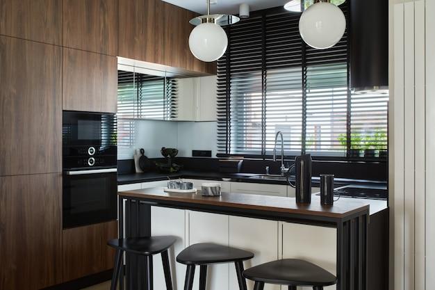 빌트인 주방과 주방 아일랜드가 있는 미니멀한 현대적인 갈색 패널 주방 인테리어. 기하학적 형태와 모양. 주형.