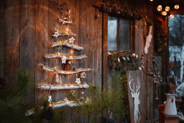 Минималистичная современная модная рождественская елка на деревенском деревянном фоне. елочные игрушки своими руками в деревенском скандинавском стиле.