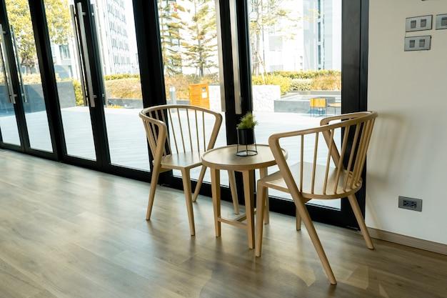 Минималистичный современный интерьер светлой комнаты. стол и стулья у большого окна.