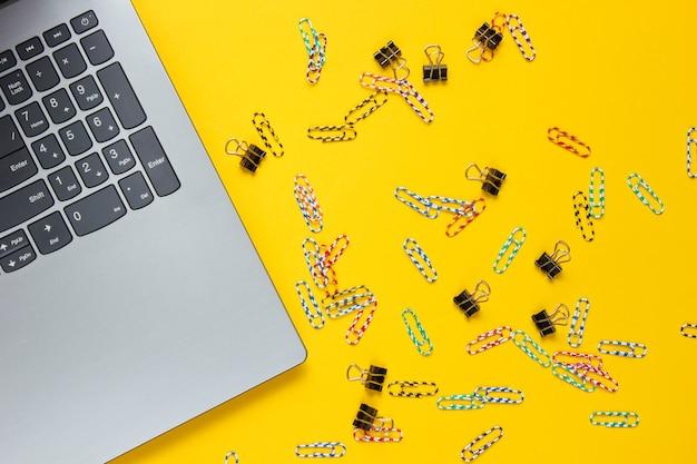 ミニマルなオフィスの静物。ノートパソコン、黄色の背景にペーパークリップ。