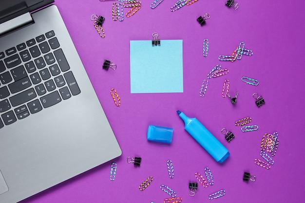 Минималистичный офисный натюрморт. ноутбук, канцелярские товары на фиолетовом фоне.