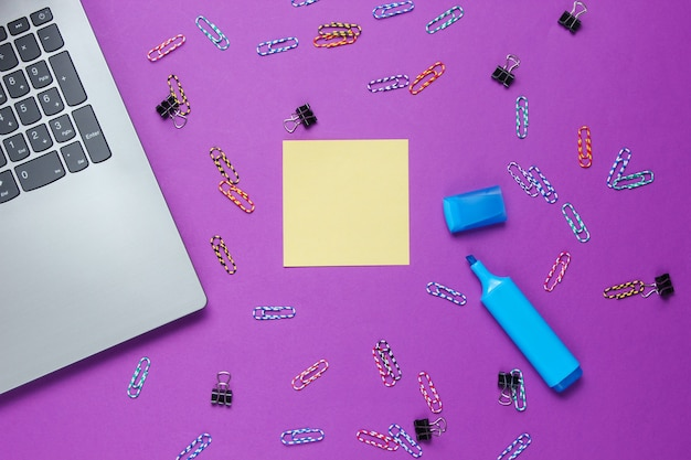 ミニマルなオフィスの静物。ノートパソコン、紫色の背景に文房具。