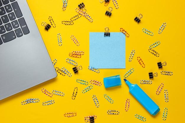 ミニマルなオフィスの静物。ノートパソコン、黄色の背景に文房具。