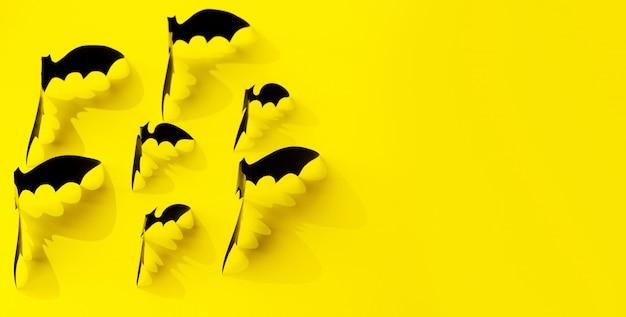 Minimalistic paper bat pattern with falling shadow on yellow.