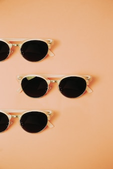 Minimalistic pattern of a pair of sunglasses over a pastel orange background  , design and summer concepts