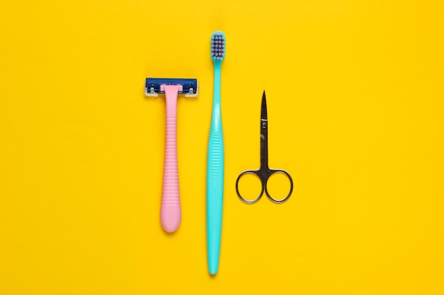 Minimalistic personal care, beauty concept. plastic razor, toothbrush, nail scissors on a yellow. top view