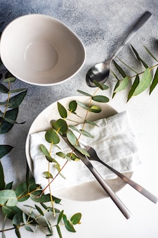 Minimalistic place setting with fresh eucalyptus leaves on concrete table