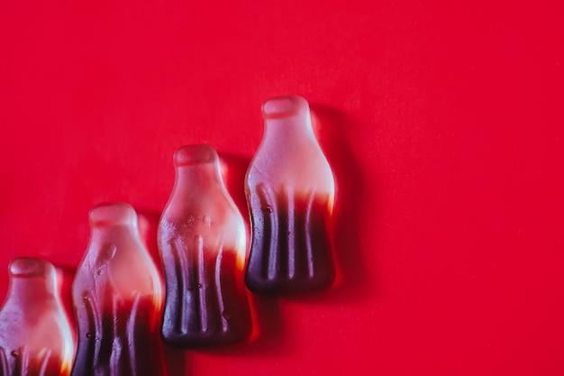 젤리 콜라 사탕이 있는 최소한의 빨간색 배경