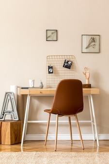 모의 사진 프레임, 나무 책상, 갈색 의자, 식물, 사무실 및 개인 액세서리가 많은 홈 오피스 공간의 미니멀리즘 스칸디나비아 인테리어. 세련된 중립 가정 장식. 주형.