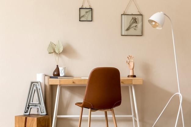 사진 프레임, 나무 책상, 갈색 의자, 디자인 램프, 사무실 및 개인 액세서리를 모의하는 홈 오피스 공간의 미니멀리즘 스칸디나비아 인테리어. 세련된 중립 가정 장식. 주형.