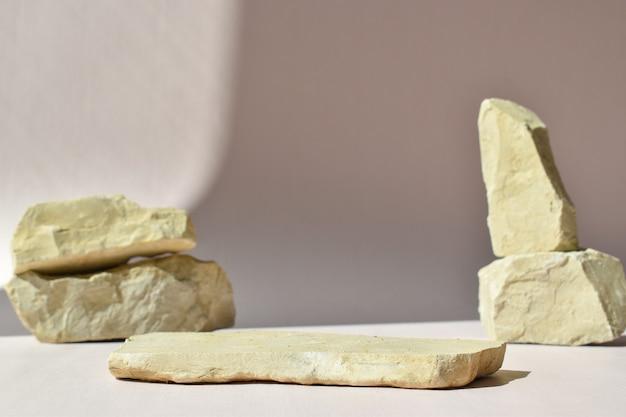 돌의 배경에 누워 있는 돌의 최소한의 장면. 제품 및 화장품 프레젠테이션을 위한 패션쇼. 천연 제품을 위한 무대가 있는 쇼케이스. 에코 위빙. 자연스러운 그림자. 프리미엄 사진