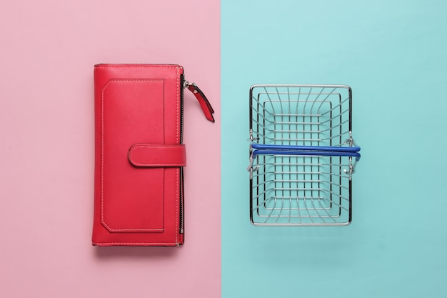 Minimalistic shopping concept mini shopping basket and red leather wallet on pink blue background
