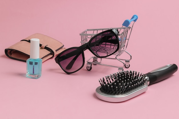 Minimalistic shopping concept mini shopping trolley with female accessories