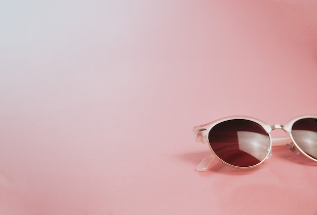 Minimalistic shot of a pair of sunglasses over a pastel pink background  , design and summer concepts