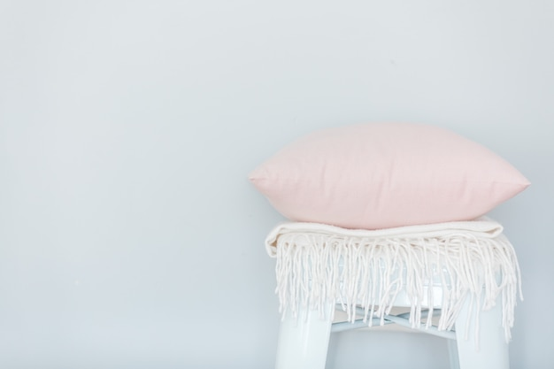 Minimalistic skandinavian picture of a light pink pillow and a white plaid on the chair near a pale blue wall