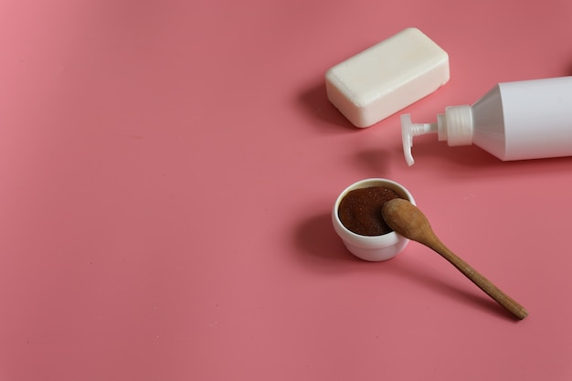 Minimalistic spa composition with natural scrub, dispenser bottle and soap on pink background, copy space.