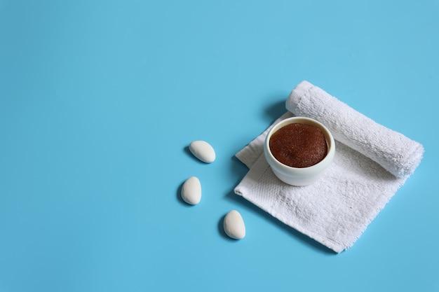 Composizione minimalista spa con scrub naturale e asciugamano su sfondo blu, spazio copia, concetto di cura della pelle del viso e del corpo.