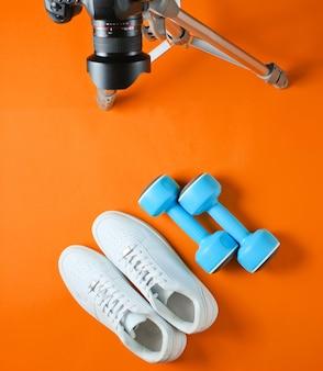 Минималистичная спортивная концепция. фитнес-блоггинг. белые кроссовки с пластиковыми гантелями и фотоаппаратом со штативом на оранжевом фоне. вид сверху