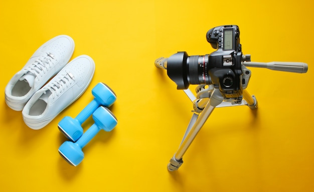 Minimalistic sport concept. fitness blogging. white sneakers with plastic dumbbells and camera with tripod. top view