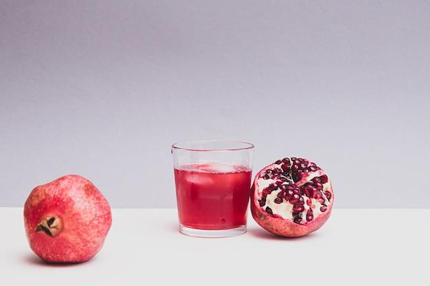 석류 열매와 석류 주스가 유리에 담긴 최소한의 정물