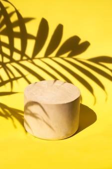 제품 디스플레이를 위해 야자수 잎으로 음영 처리된 노란색 배경의 미니멀한 석조 연단