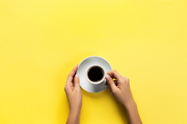 Minimalistic style woman hand holding a cup of coffee on yellow background. flat lay, top view