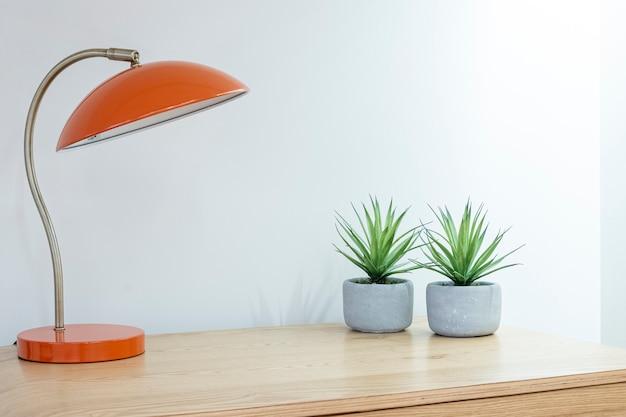 Минималистичный стильный интерьер в стиле бохо с лампами и комнатными растениями на деревянном ночном столике