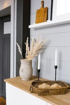 주방의 미니멀하고 세련된 현대적인 스칸디나비아 장식. 꽃병에 말린 꽃, 검은 촛대에 흰색 초, 바구니에 빵