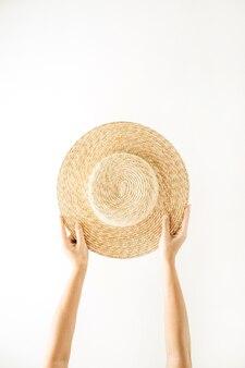 ミニマルな夏と旅行のコンセプト。麦わら帽子をかぶった女性の手。孤立した最小限の背景