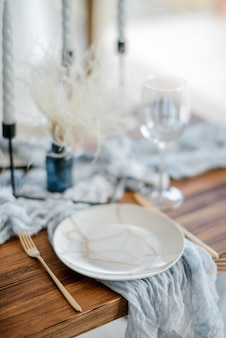 休日の夕食、ドライフラワー、プレート、黄金のカトラリー、白い燭台、明るい青いテーブルランナーの木製テーブルのミニマルなテーブルの設定。セレクティブフォーカス。