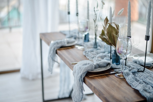 Minimalistic table setting for holiday dinner, wooden table with dried flower, plates, golden cutlery, white candeles, bright blue table runner. selective focus.