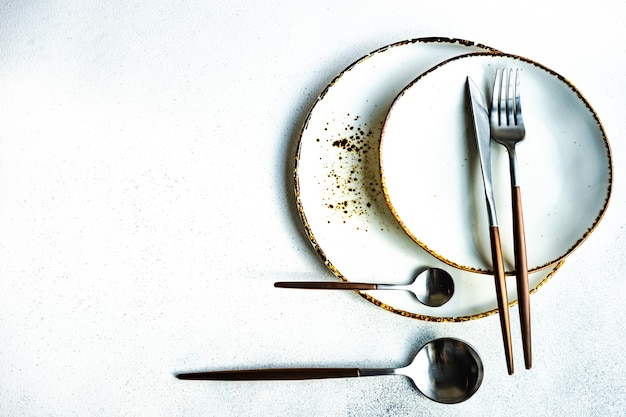 Минималистичная сервировка стола в пастельных тонах с деревенскими тарелками и современными столовыми приборами на белом бетоне