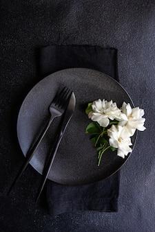 Минималистичная сервировка стола с черной керамической посудой и столовыми приборами, украшенными цветком белой розы, на черном каменном столе с местом для копирования
