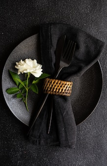 Minimalistic table setting with black stoneware and cutlery decorated with white rose flower on black stone table with copy space