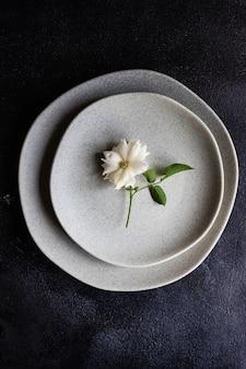 Минималистичная сервировка стола с современной керамической посудой и столовыми приборами, украшенными цветком белой розы, на черном каменном столе с местом для копирования