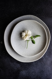 Minimalistic table setting with modern stoneware and cutlery decorated with white rose flower on black stone table with copy space