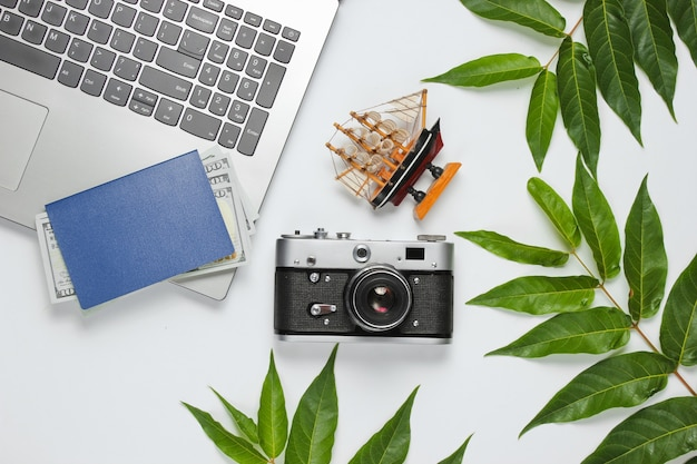 Minimalistic travel still life flat barking style. tourist traveler accessories, laptop on white background with tropical leaves.
