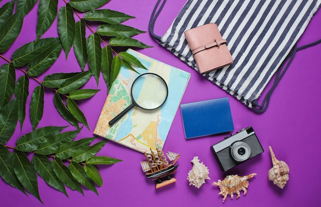 Minimalistic travel still life flat barking style. tourist traveler accessories on purple background with tropical leaves.