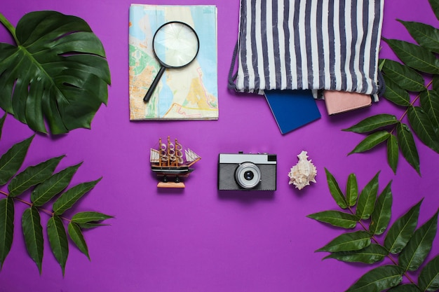 Minimalistic travel still life flat lay style. tourist traveler accessories on purple background with tropical leaves.