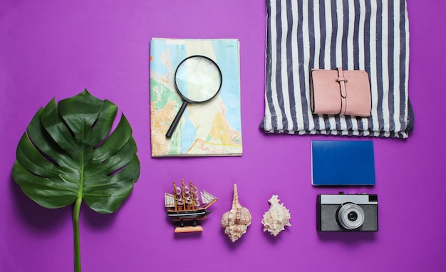 Minimalistic travel still life flat lay style. tourist traveler accessories on purple background with tropical monstera leaf.
