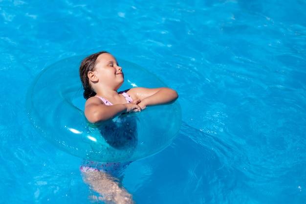 プールの青い水にミニマルなトレンドの青いインフレータブルスイミングサークル幸せな女の子